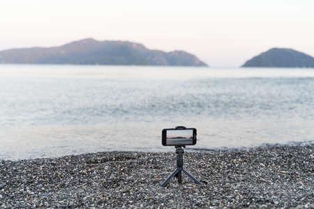 Smartphone on monopod stick. Recording video of sea sunset. Content creator