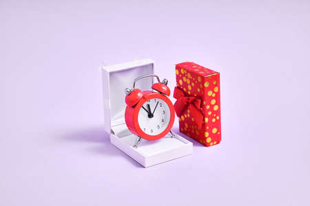 Jewelry white box and alarm clock in it. Waiting for marriage proposal. New year midnight propose.
