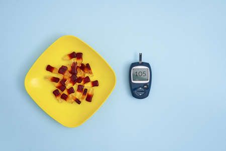 Top view of glucose meter and sweet jelly candies on blue background. Diabetes, high blood sugar level problem
