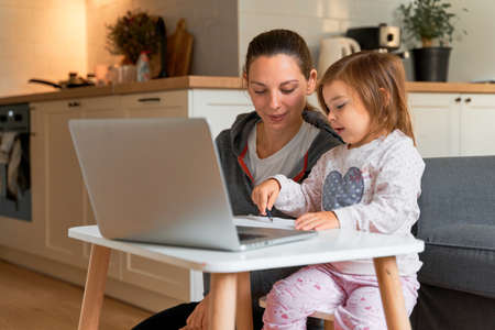 Mother and child girl sitting at home ad watching school video on laptop. Distant education, homeschooling kids.