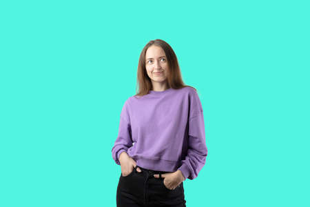 young caucasian woman on turquoise background in purple sweater. Happy millennial girl Stock fotó