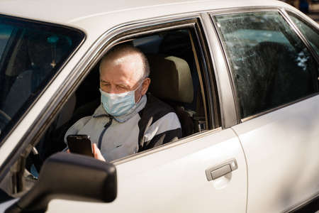 elderly caucasian man sitting in car and using phone. active modern pension people