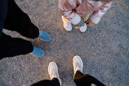 Top view of family legs on the ground outdoors. Bonding time together. Simple things
