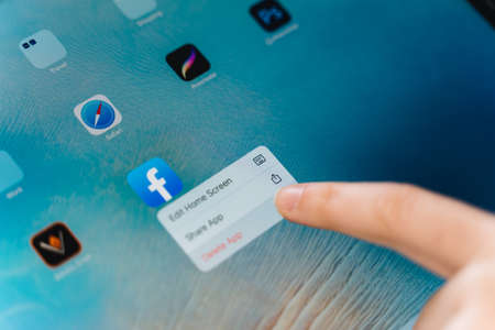 Poltava, Ukraine - jan 2021 Person deleting facebook app from phone. social media addiction. Cyberbullying online. Private data security problem Editorial