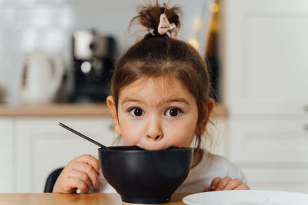 toddler girl picky eater at home kitchen. learning o eat with spoon. bad table manners of kid