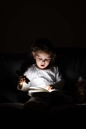 toddler caucasian girl reading book at hight with flashlight. Unplugged childhood activities. goodnight bedtime routine. reading fantasy farytale