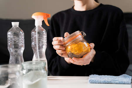 Millennial girl doing diy cleaning spray at home with vinegar, soda and lemon. Zero waste sustainable lifestyle. Environmentally friendly home. Spring cleaning