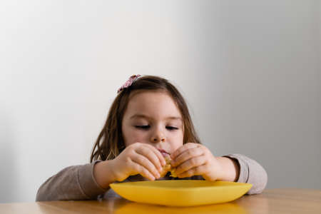 Toddler girl eating bread or pie at home with her hands. Hungry kid. Unhealthy diet. Bad table manners