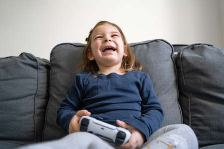Toddler girl playing video game console at home in living room on the sofa. Young gamer kid.