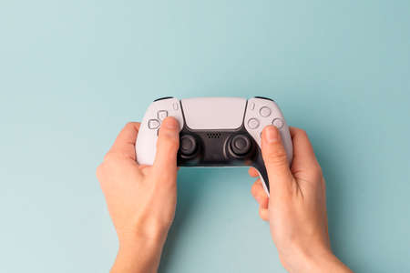Videogame console wireless gamepad. Blue background. Minimal style. Modern leisure at home.