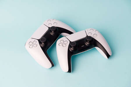 Videogame console wireless gamepad. Blue background. Minimal style. Modern leisure at home. Couple gamers