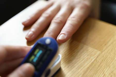 Middle age woman at home checking blood oxygen level with pulse oximeter. Banco de Imagens
