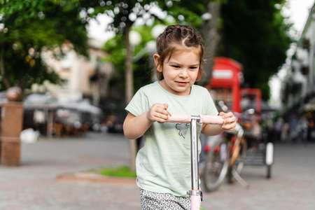 Preschool happy girl riding pink mini scooter in European city. Summer outdoors activities for kids. No helmet safety risk. Toddler play in urban areas. Sustainable parenting