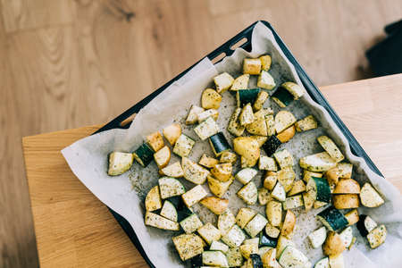 Healthy food background. Less meat concept. Vegetarian food on wooden background. Backing sheet with grilled seasoned vegetables. Lifestyle home cooking