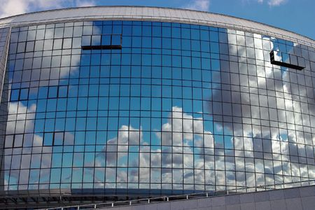 reflecting: Sky reflection in windows of modern building. Background. Stock Photo