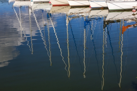 Water reflections. Masts of yachts reflected in blue water. Abstract colorful background. photo