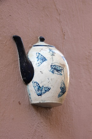 embed: A teapot, one of the teapots set embedded in facade of old building in Vilnius, Lithuania. Stock Photo