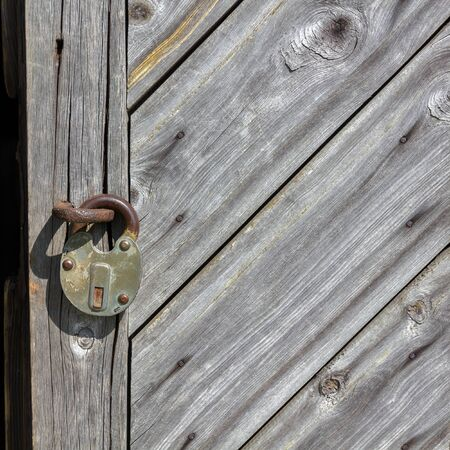 Natural wood textured background. Fragment of aged boarded door with padlock. photo