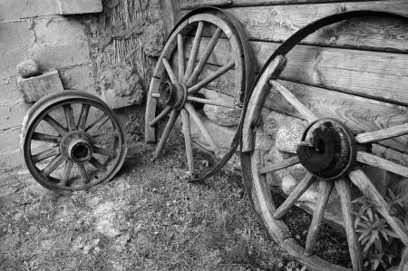 horse drawn: Old wooden wheels of cart at a barn wall