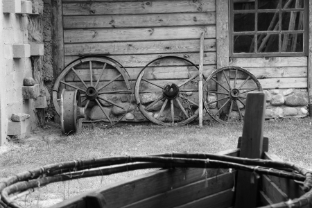 Old wooden wheels of cart at a barn wall           photo