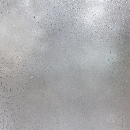 Texture of frozen drops on frosted glass. Abstract winter textured .