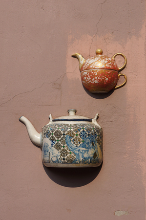 embed: Ancient teapots embedded in facade of old building in Vilnius, Lithuania.