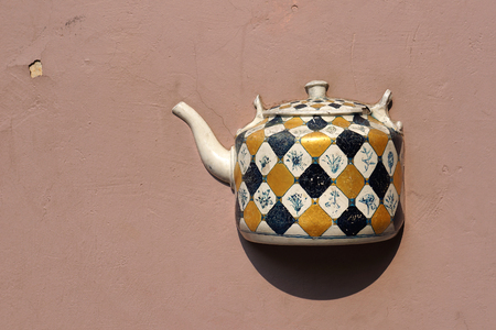 yellow tea pot: Ancient teapot embedded in facade of old building in Vilnius, Lithuania. Stock Photo