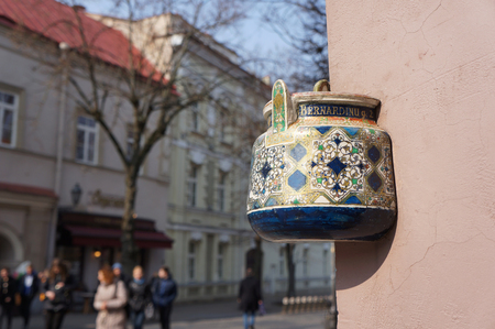 embedded: Ancient teapot embedded in facade of old building in Vilnius, Lithuania.Inscription on the teapot is address of this building - Bernardine street 2. Stock Photo