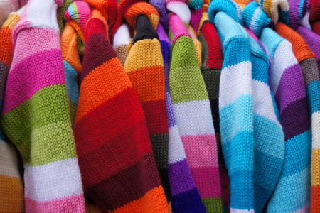 clothing rack: Colorful striped pullovers on hangers.