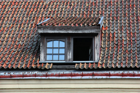 ramshackle: Windows in attic on old tiled roof. Stock Photo