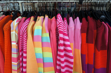 garment: Colorful pullovers on hangers. Stock Photo