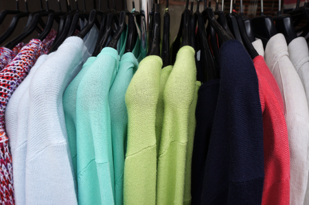 hangers: Colorl pullovers on hangers.