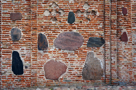 Ancient brick wall of The Kalozha church of Sts. Boris and Gleb in Grodno, Belarus, that was built in 12th century. Facade is decorated with large polished stones.