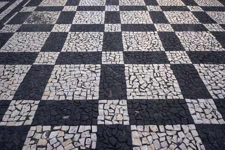 Mosaic tiles pavement pattern on streets and squares in Funchal, Madeira, Portugal.