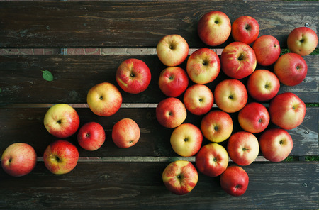 Red apples on brown wooden boards. Stock Photo