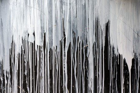 Drips of white paint on black background.