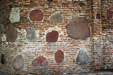 Ancient brick wall of the Kalozha church of Sts. Gleb in Grodno, Belarus, that was built in the 12th century. Facade is decorated with large polished stones.