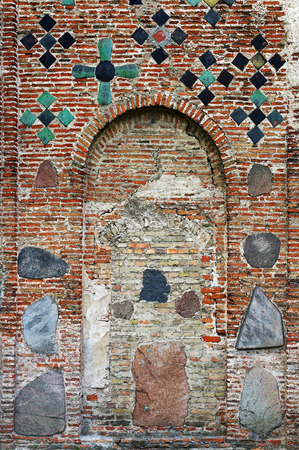 Ancient brick wall of The Kalozha church of Sts. Boris and Gleb in Grodno, Belarus, that was built in 12th century. Facade is decorated with cross-shaped majolica tiles and stones.