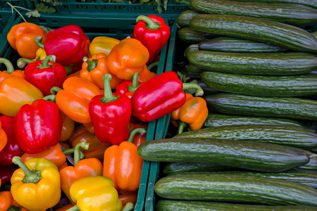 Sweet bell red peppers and cucumbers in the market. Stock Photo