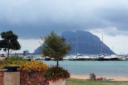 Porto San Paolo, Sardinia, Italy - August 28, 2019: Boats at quay. View to mountain of Tavolara island.