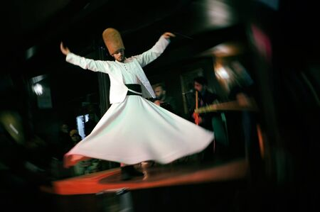 ISTANBUL, TURKEY - MARCH 07, 2019: Sufi whirling dervish (Semazen) is dancing on a stage. Mevlevi dance show in a cafe of Istabul.