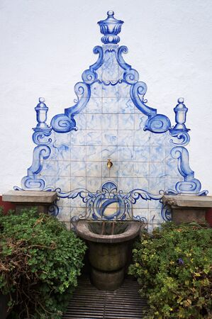 Funchal, Madeira, Portugal - June 14, 2017: Drinking water source decorated traditional portuguese ceramic tiles on a street of Funchal.