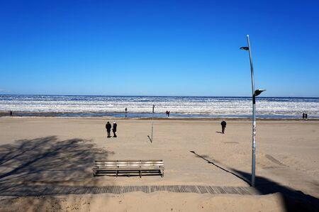 JÅ«rmala, Riga region, Latvia - March 27, .2018: People walking along beach. Ice hummocks on Baltic Sea in JÅ«rmala, Latvia.