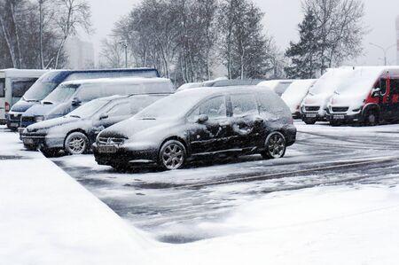 Minsk, Belarus - December 27, 2019: Winter urban scene. Snowfall and cars on parking.