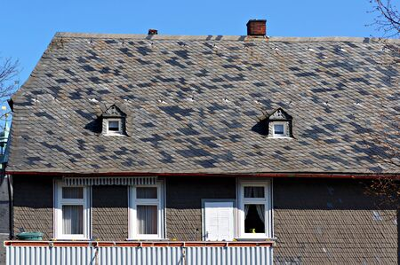 Goslar, Germany - April 21, 2016: Medieval house in the historical center of Goslar. Roof and wall covered with natural black slate tiles.