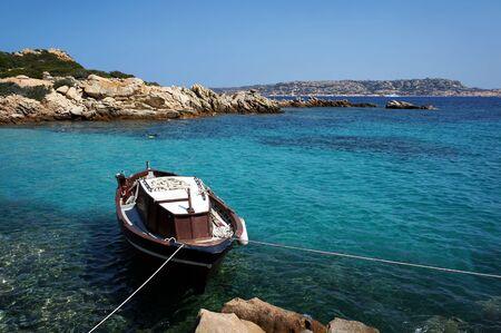 Paisaje marino con barco en vívidas aguas turquesas. Archipiélago de La Maddalena en Cerdeña, Italia.