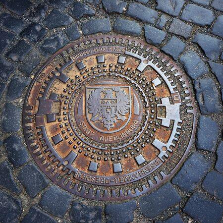 Quedlinburg, Germany - April 22, 2016: Emblem of Quedlinburg on metal manhole cover.