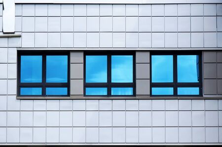 Facade of modern building. Reflection of blue sky in windows glass. Standard-Bild