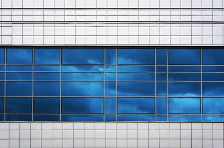 Facade of modern building. Reflection of blue sky in window glass. Reklamní fotografie