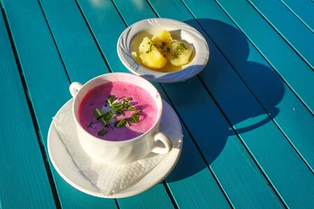 Cold beetroot soup with sour cream, greens and hot potatoes. Selective focus.